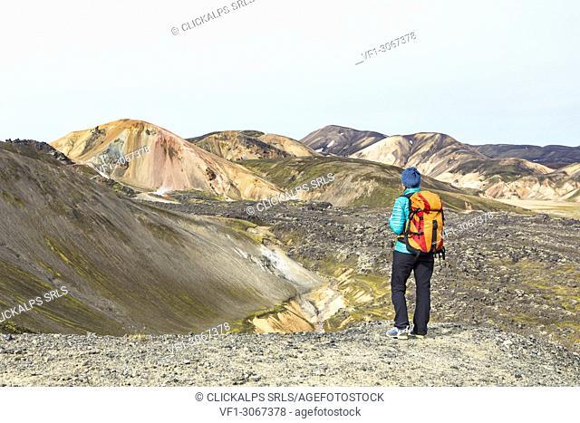 A trekker is looking at the Landmannalaugar panorama walking up to the Blahnukur mountain (Landmannalaugar, Fjallabak Nature Reserve, Highlands, Southern Region
