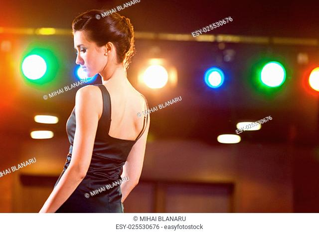 Beautiful and feminine pose of a refined brunette lady in black elegant dress, seen from behind..