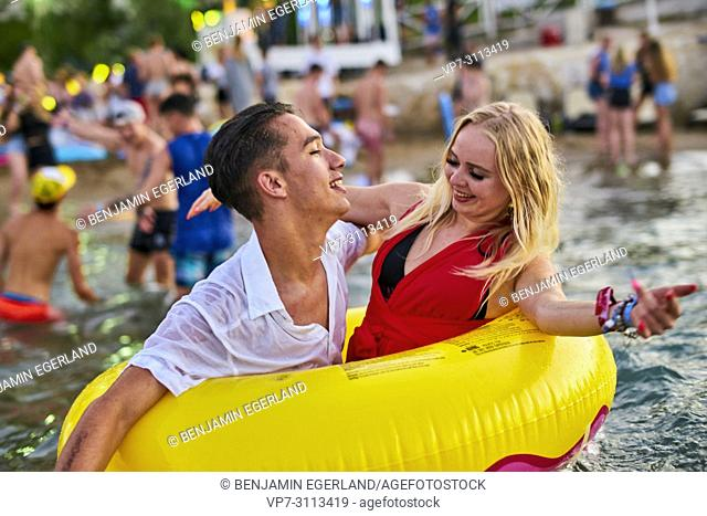 Greece, Crete, Chersonissos, couple at Beach Party in sea, inflatables
