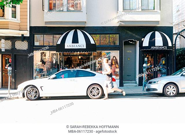Boutique front with parking cars and running man