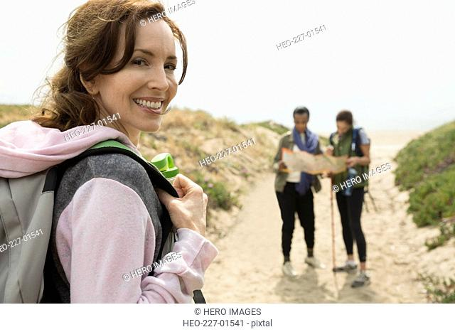Portrait smiling woman with backpack hiking with friends