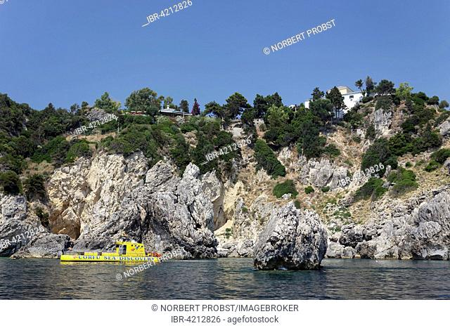 Cliffs and a glass bottom boat, Monastery of Panagia Theotokos tis Paleokastritsas above, on rocks, Paleokastrista, island Corfu, Ionian Islands, Greece