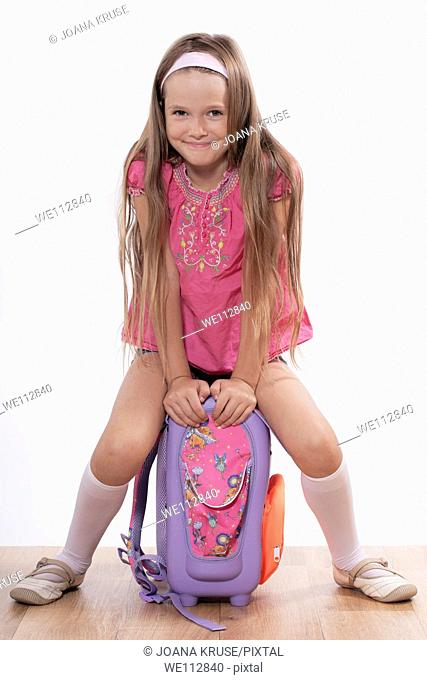 eight year old girl sitting with a satchel on the floor
