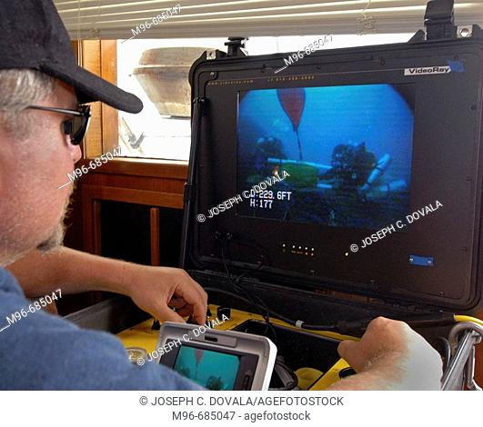 Remote operated vehicle technician observing divers with remote camera NMR Santa Barbara Channel, CA. USA