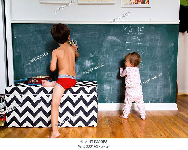 Boy, child, and toddler, girl drawing on blackboard with chalks
