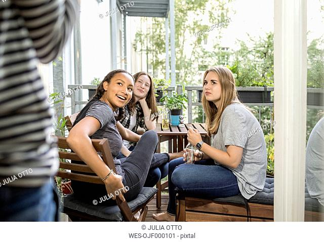 Three teenage girls sitting on a balcony looking at person at the door