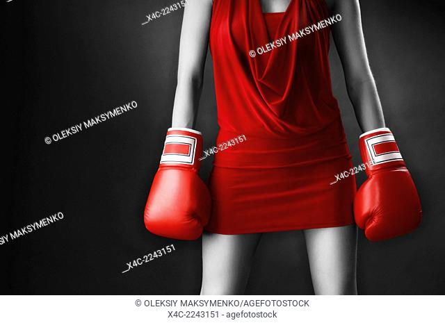 Woman in sexy red dress wearing boxing gloves. Isolated on gray background
