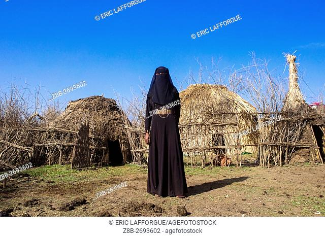 Ethiopia, Amhara Region, Artuma, an ethiopian oromo woman dressed in black burqa stands in front of her hut