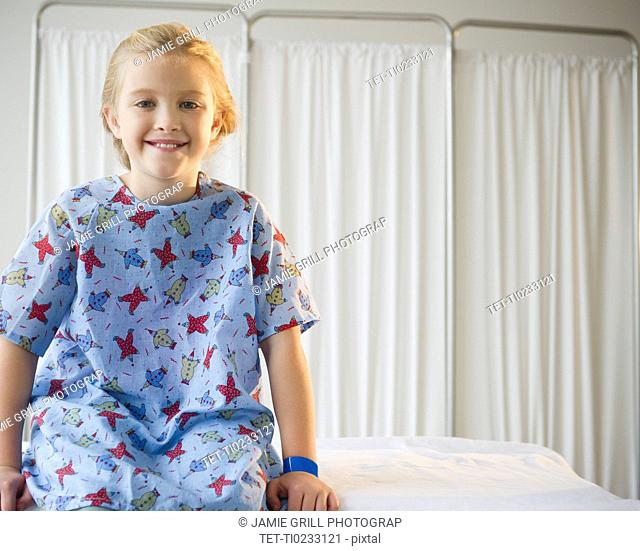 USA, New Jersey, Jersey City, Girl 8-9 sitting on hospital bed