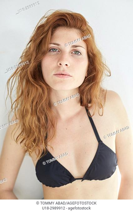 Half length portrait of young redhead woman wearing a black bikini, looking at camera