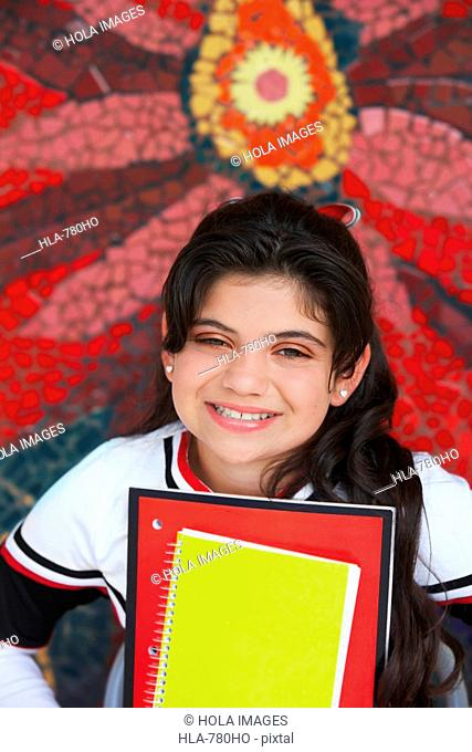 Portrait of a cheerleader holding books and smiling