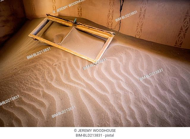 Window frame on sand dune in abandoned house