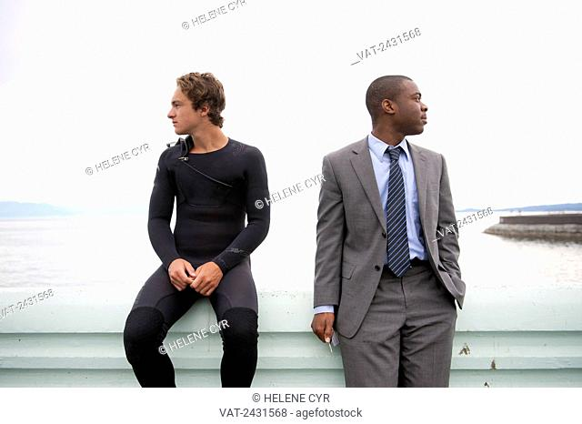 Two men of different ethnicities sitting on a ledge at the water's edge looking in different directions; Victoria, British Columbia, Canada
