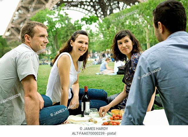 Friends enjoying picnic at base of Eiffel Tower, Paris, France