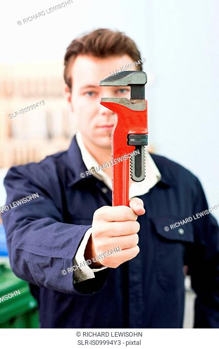 Apprentice plumber holding up adjustable wrench