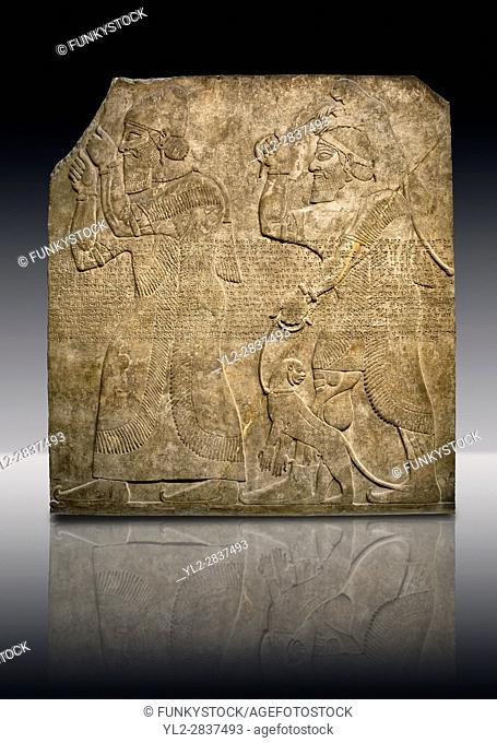 Assyrian relief sculpture panel of Tribute bearers, the first one has a turban from north-west Syria and raises his clenched hands as a token of submission