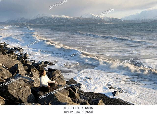Woman practicing meditation on a rocky beach, Homer Spit, Southcentral Alaska