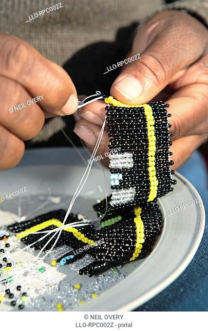 Close Up of women sewing African beaded crafts. Grahamstown, Eastern Cape Province, South Africa