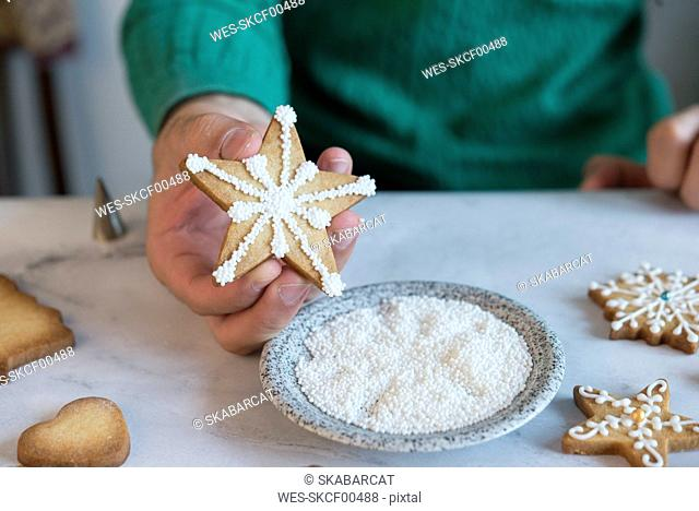Man's hand holding homemade Christmas Cookie, close-up