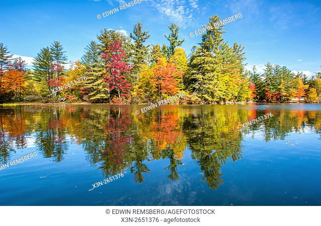 Reflections of the sky and fall foliage on Bryant Pond in Maine
