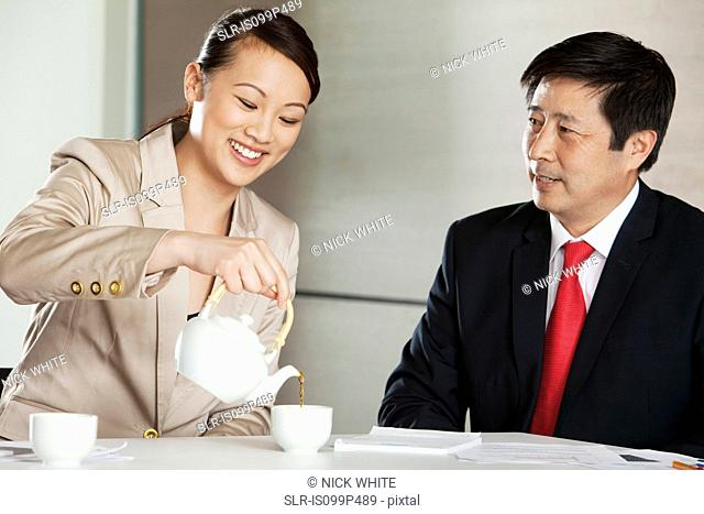 Businesswoman pouring tea for businessman