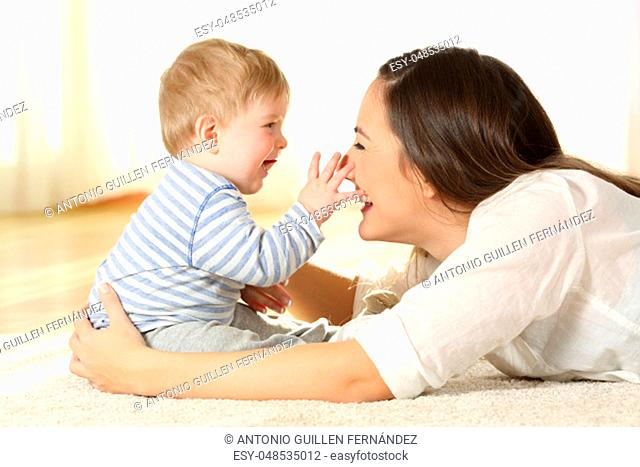 Affectionate mother and baby playing together on a carpet on the floor at home