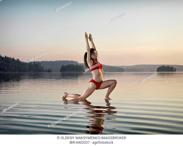 Young woman practicing Hatha yoga Low Lunge on a floating platform in water on the lake, morning light, Yoga Anjaneyasana posture