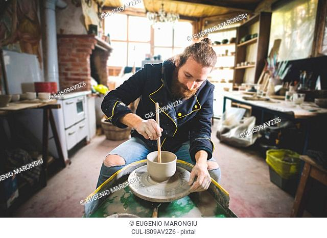 Bearded mid adult man in workshop sitting at pottery wheel using diddler to make clay pot