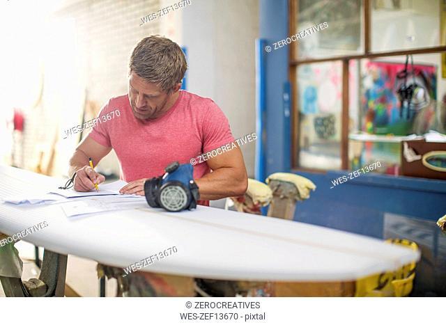 Surfboard shaper workshop, surfshop employee filling out paper work