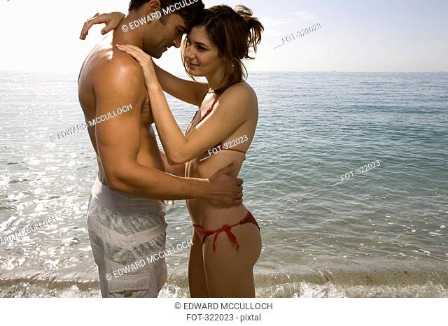 Couple embracing in front of sea