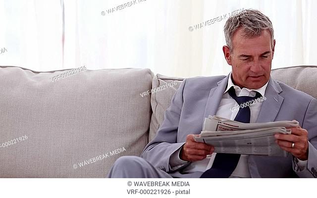Smiling businessman reading newspapers