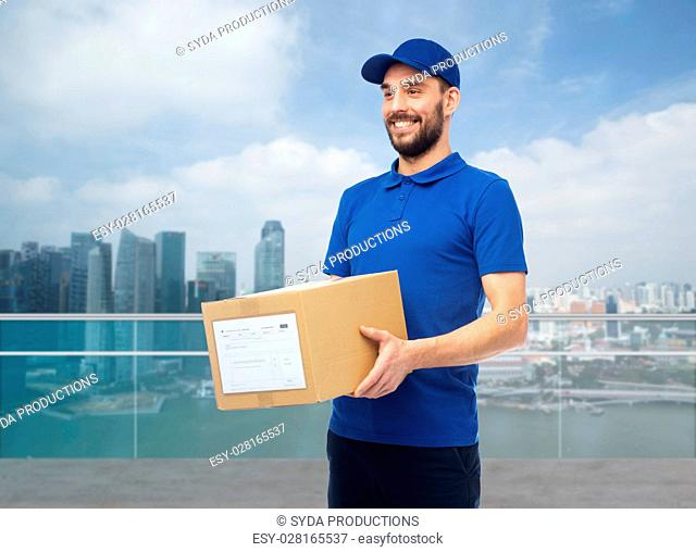 delivery service, mail, people, logistics and shipping concept - happy man with parcel box over singapore city marina bay background