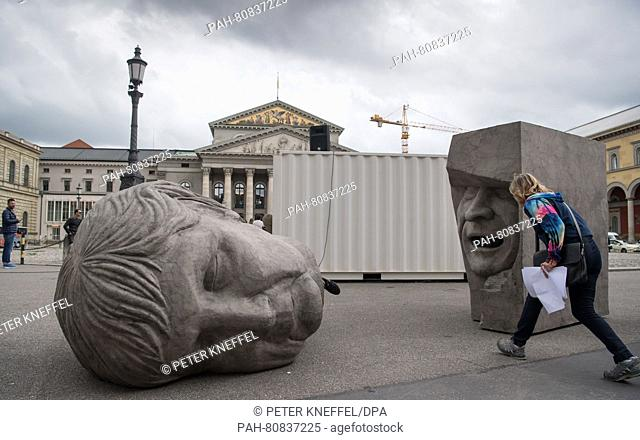 Two grey cardboard heads of Chancellor Angela Merkel (l) and Mario Draghi (r) lying in front of Bavarian state opera in Munich, Germany, 31 May 2016