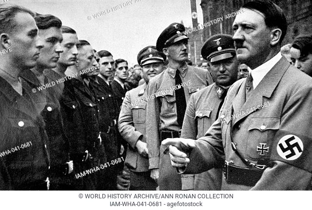 Adolf Hitler with Robert Ley 1890 – 25 October 1945) greeting young Nazi Labour Movement members 1935. Ley was a senior Nazi politician and head of the German...