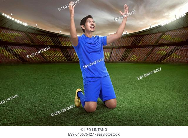 Handsome asian football player happy for winning the match on stadium