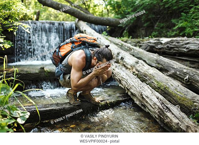 Young man on a hiking trip refreshing at a waterfall