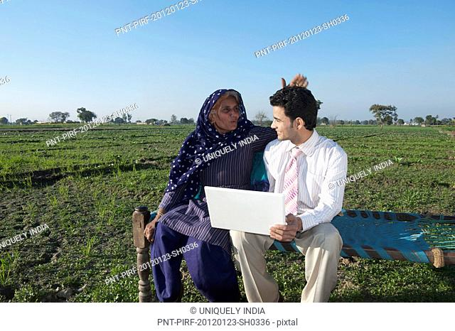 Businessman sitting in the field near his mother and using a laptop, Sonipat, Haryana, India