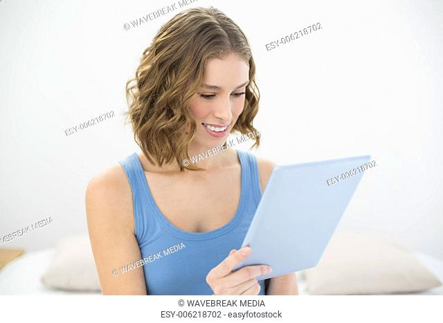 Cheerful cute woman using her blue tablet while sitting on her bed