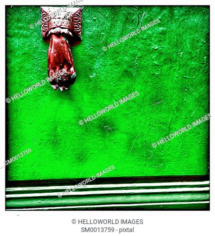 Carved hand door knocker on bright green painted door, France, Europe
