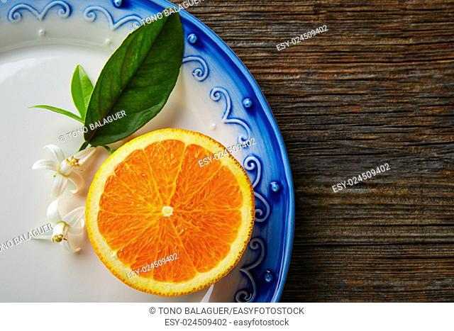 Cut half open orange fruit with orange flower on wooden table