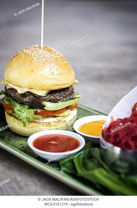 modern fusion beef burger set with lotus chips ketchup and spicy chlli sauces