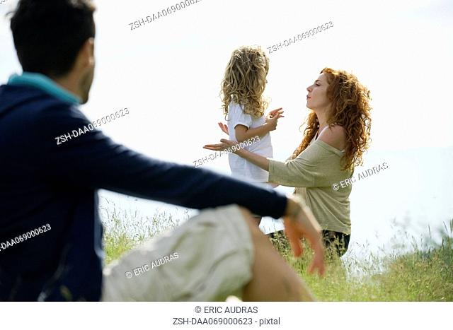 Mother talking with young daughter outdoors, father watching from foreground