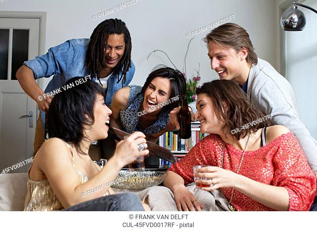 Friends laughing together in living room