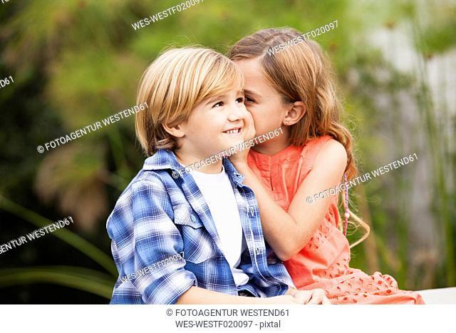 Girl whispering into boy's ear