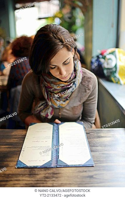 Young attractive woman looking at menu in a cafe
