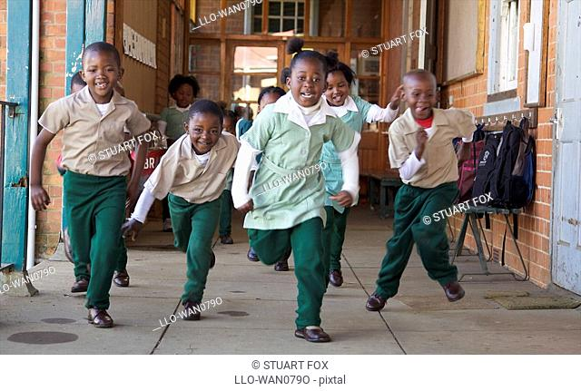 Group of schoolchildren running outside their classroom, KwaZulu Natal Province, South Africa