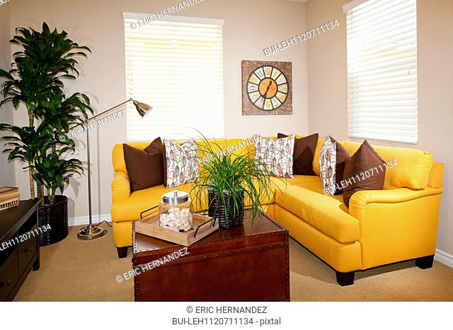 Yellow sectional sofa with wooden coffee table in living room; Azusa; California; USA