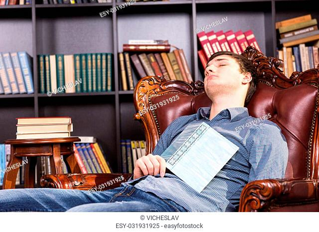 Young man enjoying a nap in the library relaxing in a comfy leather armchair with a hardcover book resting on his chest