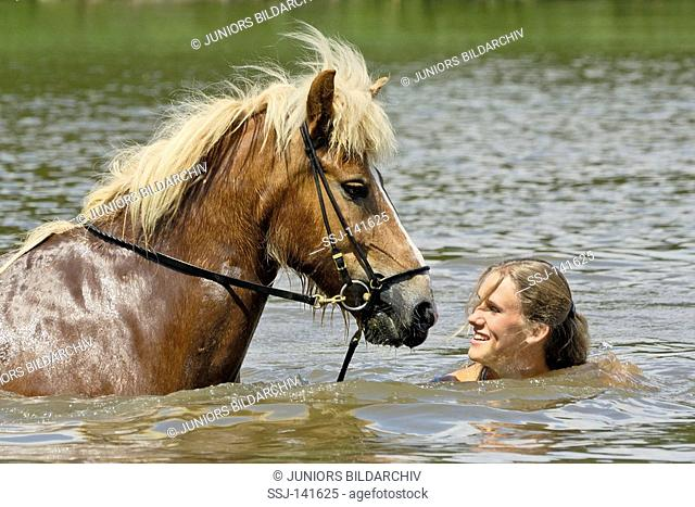 Young rider going swimming together with her Icelandic horse in a small lake in Bavaria