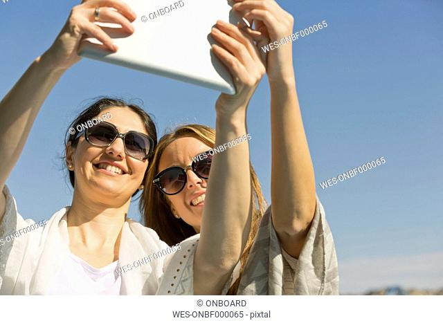 Two smiling women taking a selfie outdoors